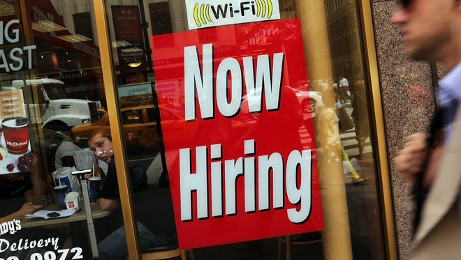 """A """"now hiring"""" sign is viewed in the window of a business."""