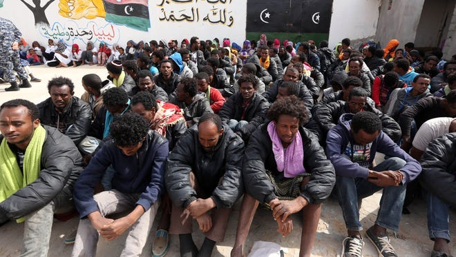 Migrants who wanted to reach Europe by boat sit at a detention center in Tripoli, Libya, on Tuesday.
