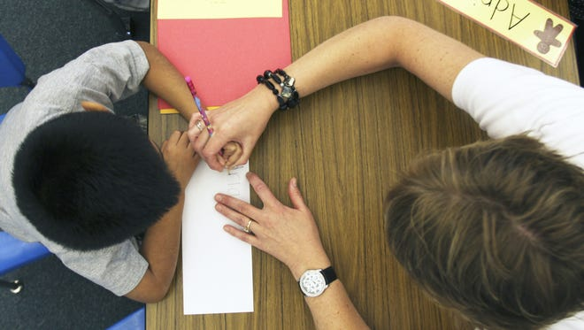 A teacher helps a student with a handwriting exercise.