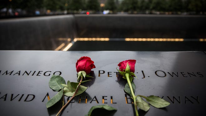 Flowers lie on 9/11 Memorial on Sept. 11, 2015, in New York.
