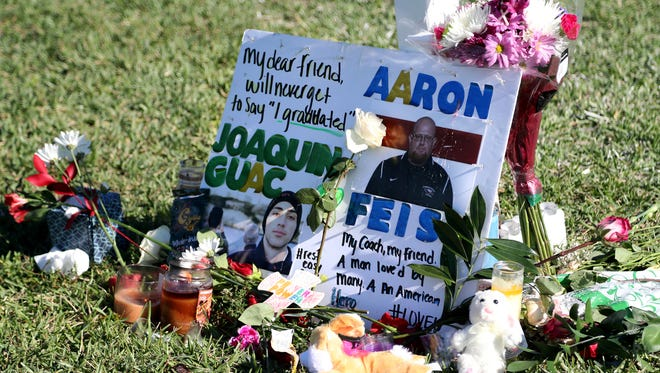 A tribute to student Joaquin Oliver and coach Aaron Feis is left at the base of a white cross at Pine Trails Park in Parkland, Fla.