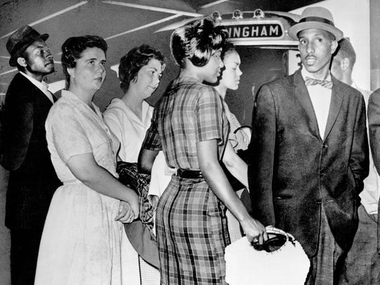 """A group of Freedom Riders from Tennessee stands at the door of a Greyhound bus in Birmingham waiting for a bus to leave for Montgomery.   5/19/1961  Archivist's note 2013: (names of riders, taken from caption of AP Wide World photo in Raymond  Arsenault's book, """"Freedom Riders."""") Left to right: Joseph Carter, Susan Hermann, Susan Wilbur, Catherine Burks, Lucretia Collins, and Bernard Lafayette. John Lewis is the partially obscured figure standing behind Lafayette."""