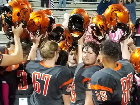 Central Kitsap football player raise their helmets in celebration after Thursday's 13-0 win over Peninsula at Silverdale Stadium.