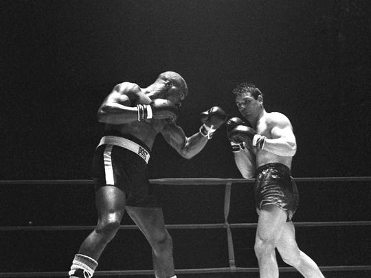 """FILE - In this Feb. 23, 1965 file photo, Rubin """"Hurricane"""" Carter, left, knocks out Italian boxer Fabio Bettini in the 10th and last round of their fight in Paris. Carter, who spent almost 20 years in jail after twice being convicted of a triple murder he denied committing, died at his home in Toronto, Sunday, April 20, 2014, according to long-time friend and co-accused John Artis. He was 76."""