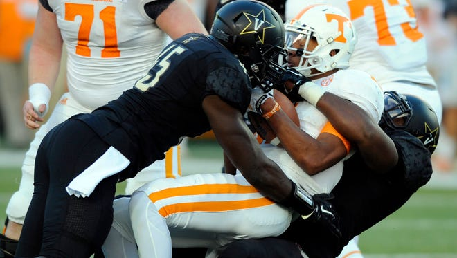 Tennessee quarterback Josh Dobbs (11) is sacked by Vanderbilt defensive lineman Adam Butler (69) and linebacker Stephen Weatherly (45) on Nov. 29, 2014.