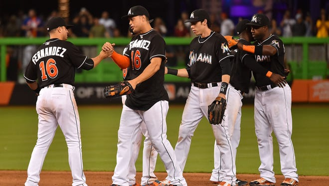Marlins teammates celebrate after defeating the Mets 7-3 on Monday, their first game following the death of pitcher Jose Fernandez.