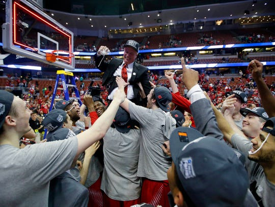 Players lift Wisconsin coach Bo Ryan after a 64-63 OT victory over Arizona sent the Badgers to the Final Four in 2014.