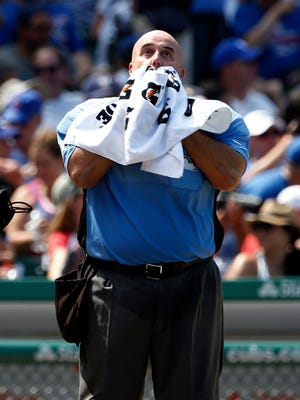 Home plate umpire Eric Cooper towels off his face during a Brewers-Cubs game on a hot and humid afternoon in Chicago.