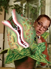 """Jared Gertner poses with Audrey II, the lovable man-eating plant in a Paper Mill Playhouse production of """"Little Shop of Horrors."""""""