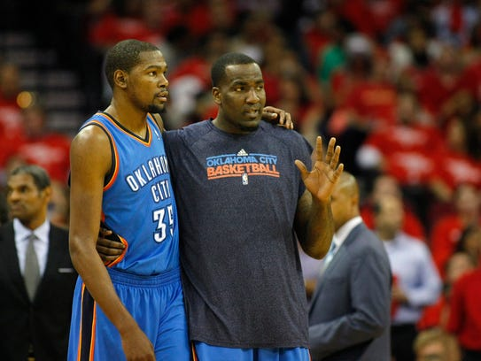 Kevin Durant talks to Kendrick Perkins during a timeout