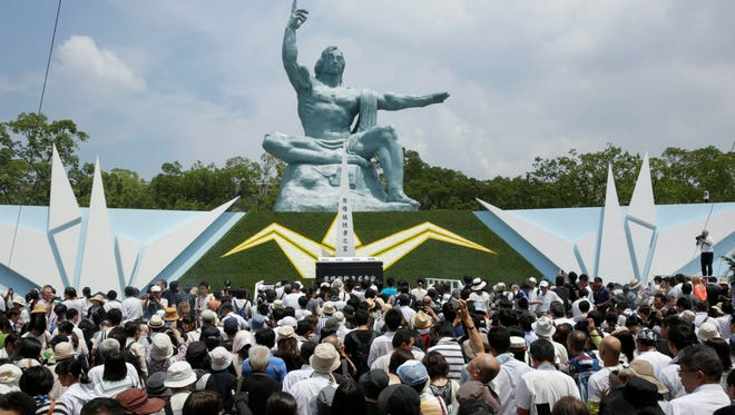 A crowd of people gathers around the Peace Prayer statue to offer prayers for victims killed by the atomic bombing of Nagasaki in 1945 after the 2015 Nagasaki Peace Ceremony.