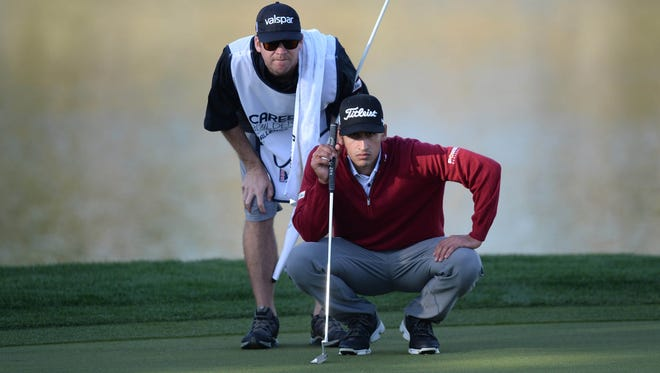 Dominic Bozzelli and his caddie David O'Donovan line up a putt on the 9th green during the first round of the CareerBuilder Challenge at PGA West Stadium Course.
