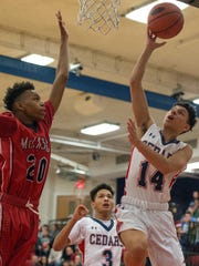 Lebanon's Carlos Rivera goes up for the basket against McCaskey's Marcus Benning In the Cedars' 59-50 win Friday.