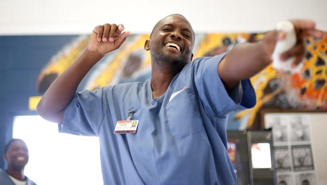 Joseph Montique sings Bob Marley's Three Little Birds Monday with fellow inmates enrolled in the Music Therapy Program at the Wakulla Work Camp Correctional Institution. Their performance, entitled the Behind the Wire Choir, was the culmination of months of practice with program creator Lorna Segall.