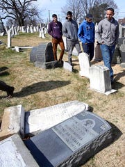 FILE - In this Monday, Feb. 27, 2017 file photo, volunteers from the Ahmadiyya Muslim Community survey damaged headstones at Mount Carmel Cemetery in Philadelphia. More than 100 headstones have been vandalized at the Jewish cemetery, discovered less than a week after similar vandalism in Missouri, authorities said.