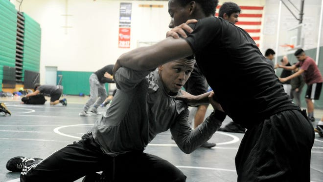 Willie Dillon Jr., left, wrestles Ryan Harris during a recent Pacifica High practice. The sophomore and son of the head coach, Willie Sr., took up wrestling in his freshman season.