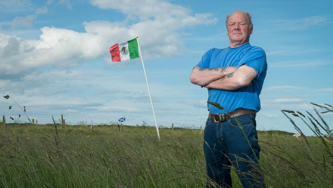 Michael Forbes poses for a photograph beside the Mexican flag he erected alongside Donald Trump's International Golf Links course, north of Aberdeen on the East coast of Scotland, on June 21, 2016.