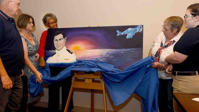 A painting was unveiled Thursday honoring U.S. Navy Lt. Marion William Dufilho, a 25-year-old World War II pilot and Opelousas native who went missing in action near the East Solomon Islands on Aug. 24, 1942.  The painting will be on display at the St. Landry Parish Veterans Memorial. Attending the ceremony were Dufilho family members, from left, Jerome Gaudet,  Jeri Dufilho Cortez, Pat Mason-Guillory, Rose Dufilho Guillory, along with Charlotte Langlois, a Magnet Academy for the Cultural Arts student who painted the mural.