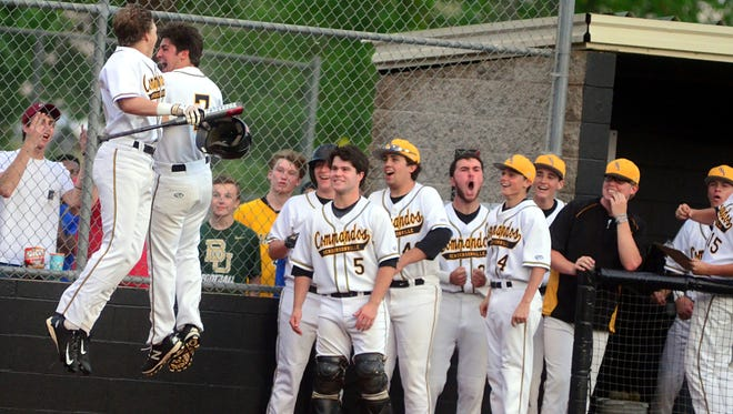Hendersonville High senior Jon Swindle (7) and Commando teammates celebrate with sophomore Brett Coker (at left) after his first-inning home run on Tuesday evening.