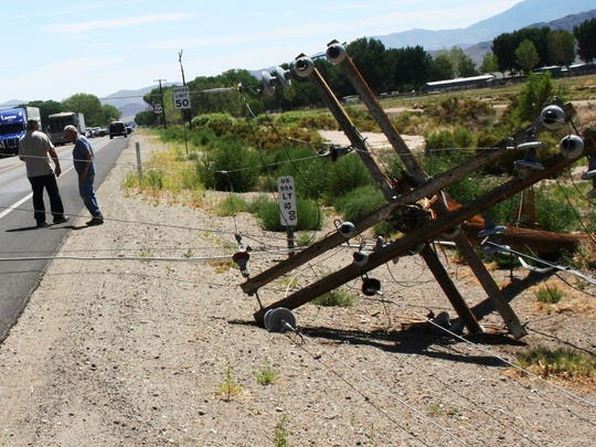 Two men who were in a vehicle that drove into the power lines, foreground, shortly after the poles snapped and lines fell over the highway in Yerington, wait to fill out reports Wednesday morning. The pickup suffered some damage.