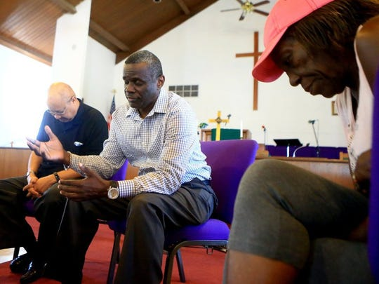 GABE HERNANDEZ/CALLER-TIMES The Rev. Adam Carrington (center) prays with other residents from the Hillcrest neighborhood Wednesday. Hillcrest residents have raised concerns over a proposed city comprehensive plan that describes the neighborhood as a special transition district.