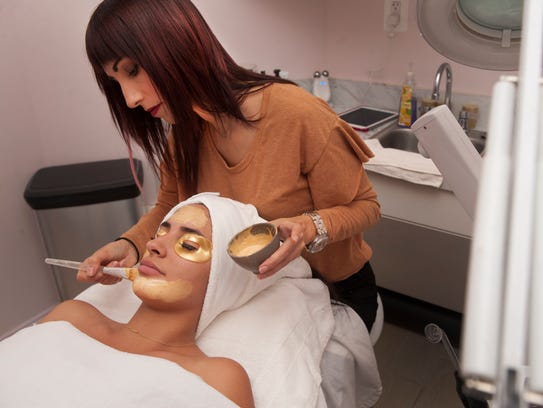 Spa owner Colleen Sparks applies a 24 karat gold facial to Lauren Badalamenti at the Dream Spa in Cherry Hill. This facial use a 24 karat gold mask that is good for most skin types, and is a unique facial to give to others this season.