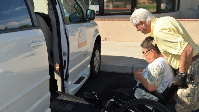 Rich Greene, a volunteer with Northwest Valley Connect, helps a senior into a vehicle to give her a ride.