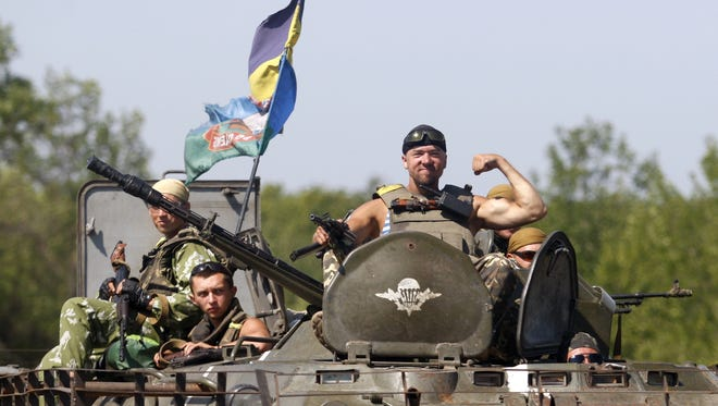 A Ukrainian soldier postures on an armored personnel as troops have reportedly surrounded the pro-Russian rebel stronghold of Donetsk on Aug.  9, 2014.