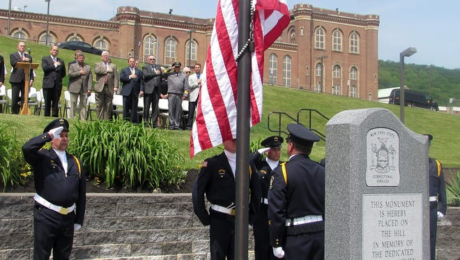 The American flag is lowered to half mast during a memorial service Friday at the Elmira Correctional Facility.