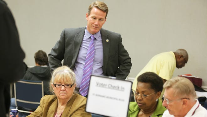 Ohio Secretary of State Jon Husted watches St. Bernard poll workers Gail Webb, Phyllis Austin and Ken Beringhaus use the new electronic voter sign-in system on Nov. 3.