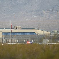 Police lights are seen in the distance after several days of unrest at the Arizona State Prison-Kingman.