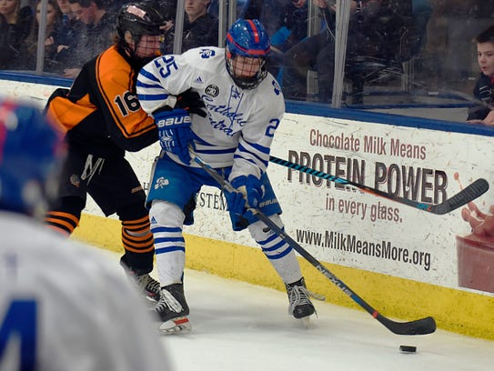 CC's Brendan West (right) controls the puck on the