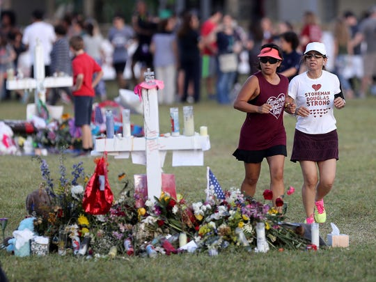 Runners run past the memorial for the victims of last