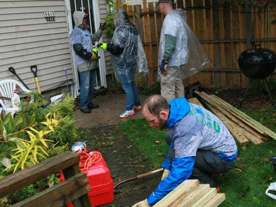 Sam Gilbert, a volunteer with Revitalize Milwaukee, helps build a wheelchair ramp Saturday in a neighborhood project that attracted more than 100 volunteers on the city's northwest side.