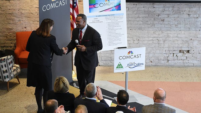 Rich Jennings, senior vice president of Comcast's mountain region, shakes hands with Ann Hutchison, executive vice president of the Fort Collins Area Chamber of Commerce at Galvanize on Thursday, May 19, 2016. Comcast announced it will open a call center at the former Hewlett-Packard campus, bringing 600 jobs to Fort Collins.