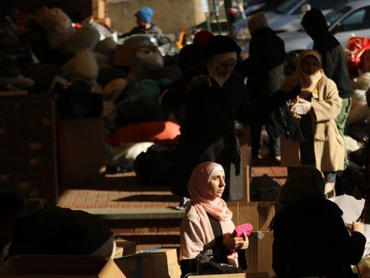 Zaineb Hamdeh, 17, of Brooklyn folds donations to be