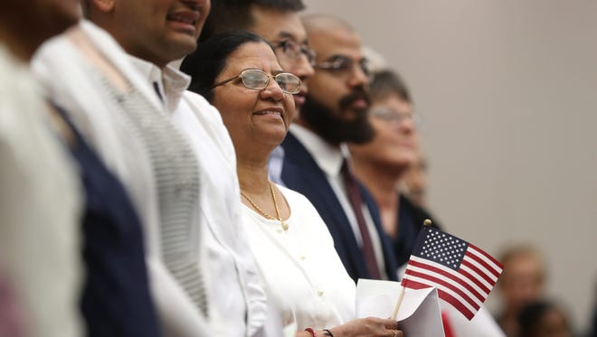 Muktaben Kantilal Prajapati smiles as she is sworn in by the U.S. Citizenship and Immigration Services with a group of 75 newly naturalized citizens during a ceremony at the U.S. District Court downtown on Thursday, May 17, 2018.