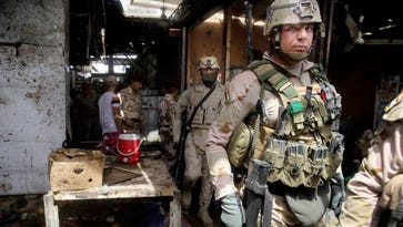 Security forces inspect the scene after a bomb explosion at an outdoor market in Baghdad's northern neighborhood of Shaab, Iraq, on May 17, 2016.
