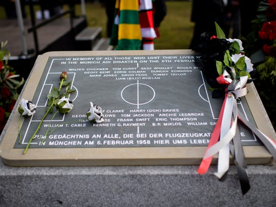 Flowers lie on a memorial during a commemoration ceremony on the Manchester place at the Munich Riem airport, southern Germany, Tuesday, Feb. 6, 2018. Sixty years ago on Feb. 6, 1958 a plane with professional players of the Manchester United soccer club on board crashed in Munich with 21 survivors and 23 fatalities. (Matthias Balk/dpa via AP)