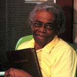 Oseola McCarty sits on the front porch holding her Bible at her home in Hattiesburg in this July 1995 photo. McCarty donated $150,000 to the University of Southern Mississippi from earnings she received from ironing and cleaning clothes.