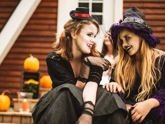 Young vampire and witch dressed up for halloween