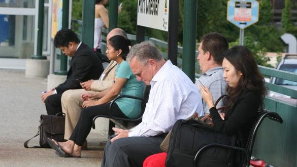 Commuters Dan Smith from Greenwich, Conn. and Victoria Kim from Rye Brook check out their electronic devices at the Port Chester train station, Aug, 20, 2014.  When Metro-North has service disruptions, commuters frequently turn to social media to voice their frustration and get information.