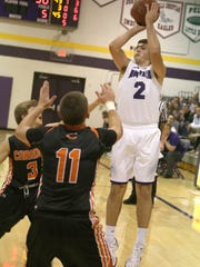 Norwalk senior Matt Guessford puts a jump shot over Carroll sophomore Cooper ross and junior Kolby Molinsky. Norwalk beat Carroll 59-58 on a final minute shot by Guessford in a Dec. 21 home game.
