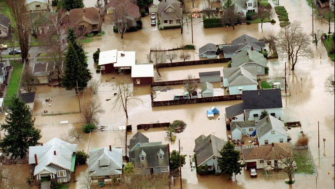 Floodwaters from Mill Creek fill neighborhood streets in Salem on Feb. 8, 1996