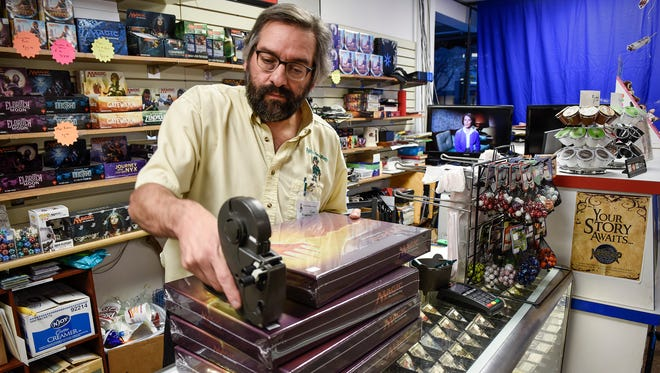 Gino Marinaro, Paddy's Game Shoppe, prices new games to put on the shelves this week in anticipation of Small Business Saturday.