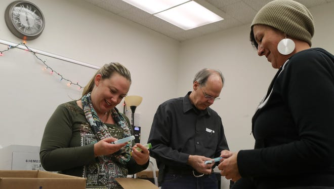 Teri Zanni, master of social work at the Redding Homeless Day Resource Center, from left, treasurer Rick Roberts and volunteer Kayla Patterson sort through donated personal care items Thursday at the Shasta County Community Health Center's Patient Education Outreach and Enrollment Center. The health center is starting a pilot project Saturday to make hot showers available to the homeless population in Redding.