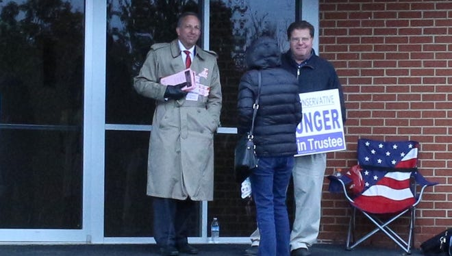 Colerain Township trustee candidates Jeff Ritter and Dan Unger talk with a candidate at White Oak Christian Church. Incumbent Ritter lost and Unger, who served on the Northwest Board of Education, was elected to the board of trustees.