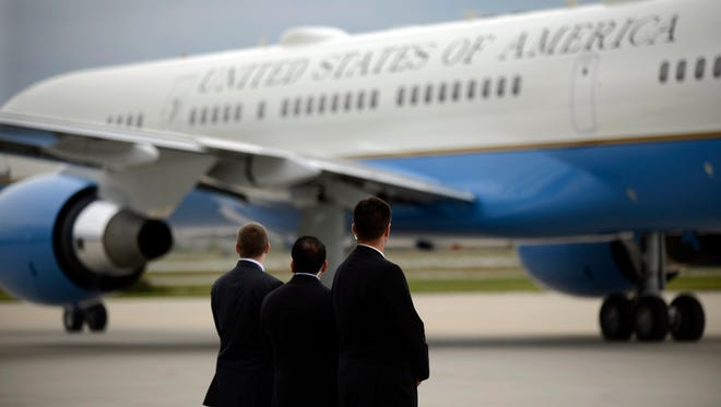 FILE- In this Oct. 2, 2014, file photo, members of the Secret Service watch as Air Force One taxies on the runway before leaving the Gary/Chicago International Airport in Gary, Ind. In the space of just a few months, the reputations and approval ratings of the Centers for Disease Control and Prevention, Secret Service, as well as the Veterans Administration, have been seen a decline. (AP Photo/Paul Beaty, File)