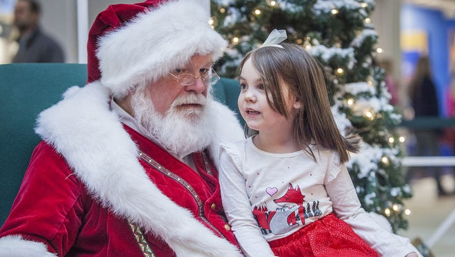 Santa consults with a youngster at Muncie Mall in this file photo.