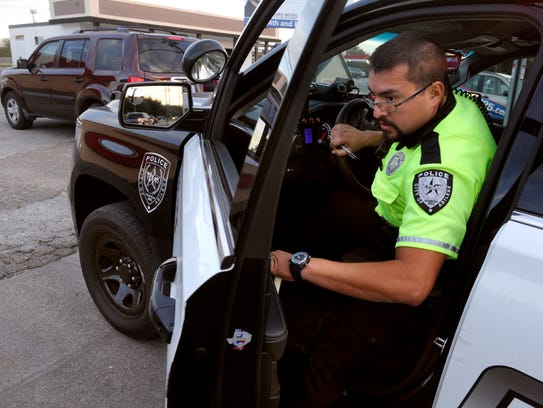 Michael Garcia, a traffic officer with the Abilene Police Department, gets out of his patrol vehicle to speak with a motorist.